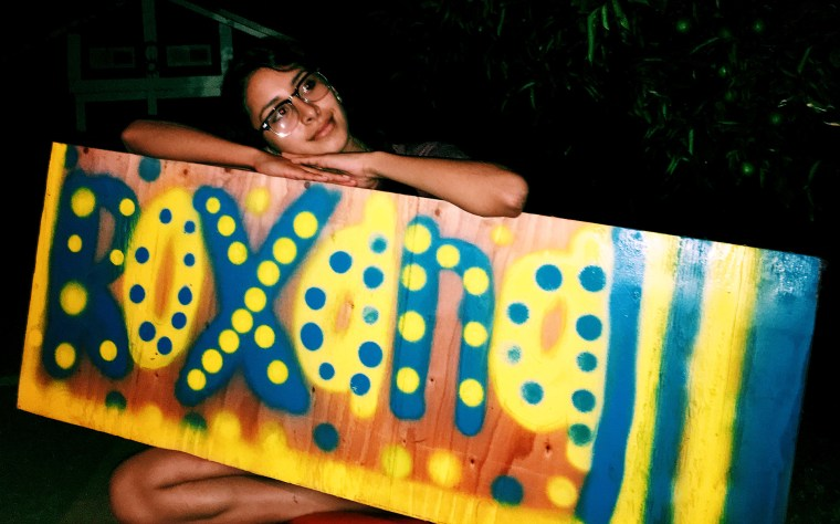 Roxana Chavez holding a piece of plywood with her name spray painted in bubble letters and polka-dots