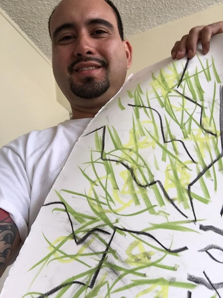 Samuel De La Cruz with a pastel on paper line drawing