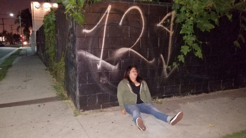 Selenara imagining a death by gunshot - image with blood on forehead and leaning up against a low wall