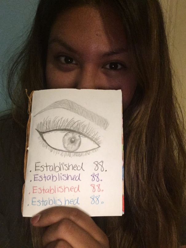 "Claudia Sanchez holding a small zine she made called ""Established '88"""