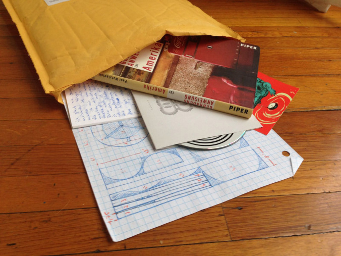 a large tan envelope filled with various bits of ephemera including a drawing, a letter, and a CD