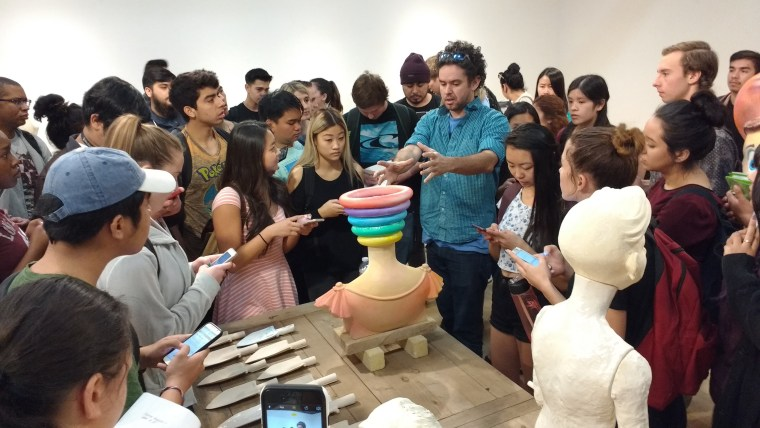 Samuel Jernigan discussing work with a crowd of students
