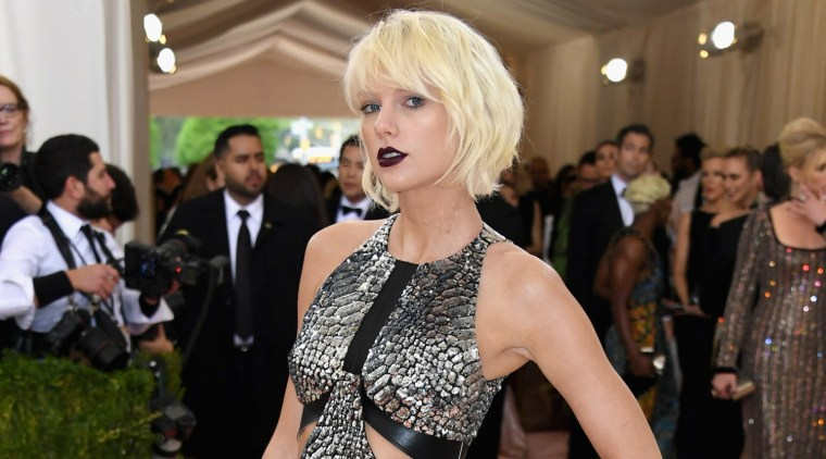 Taylor Swift in a metallic silver dress and strappy boots walking the red carpet at the 2016 Met Gala at the Metropolitan Museum of Art on Monday,May 2, in New York City.  The 26-year-old singer is one of the co-chairs of the event with Idris Elba, Vogue editor Anna Wintour, and Apple exec Jonathan Ive.  This year's Costume Institute Gala Benefit celebrates the opening of the Manus x Machina: Fashion in an Age of Technology exhibition. Swift wears a Louis Vuitton dress, boots, and clutch, Mattia Cielo earrings, an Eva Fehren ear cuff and rings, and a Borgioni white diamond ring.