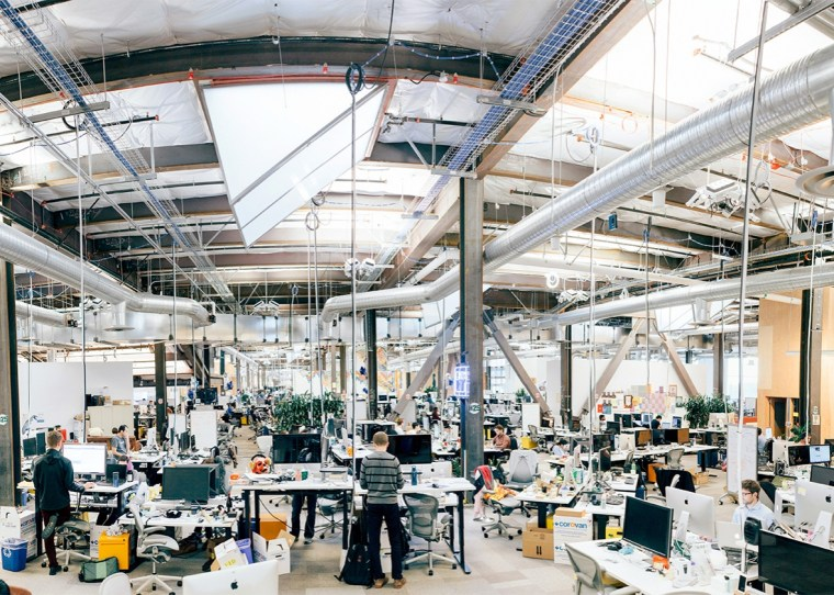 photo of large, cavernous work space at Facebook's Menlo Park offices