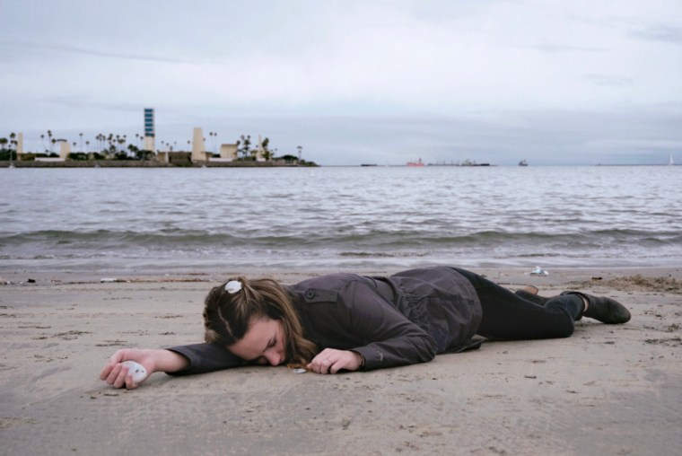 Eliza simulates her death by drowning at sea by creating a photo of her body washed up on the shore of a beach in Long Beach, CA