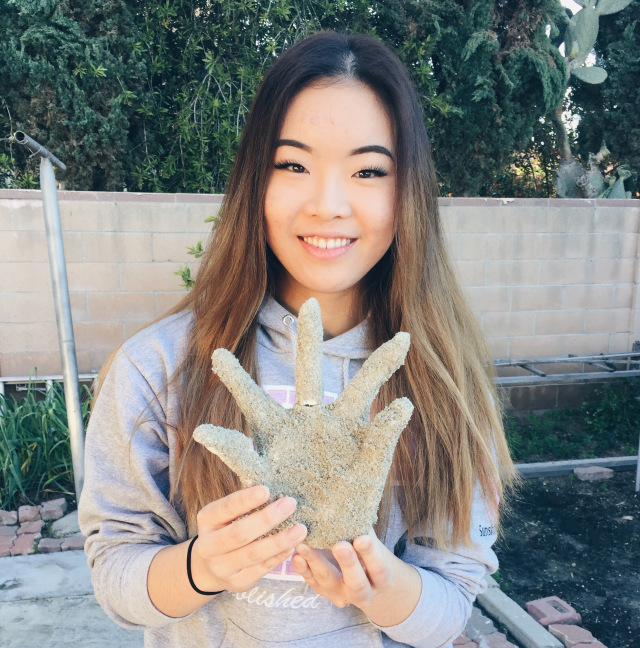Vicky Wu holding a plaster casting of her hand featuring all 5 fingers spread wide