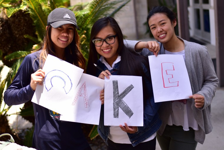 "3 students holding the letters ""C A K E"""