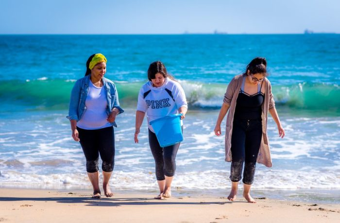 CSULB students bringing a bucket of water up from the surf