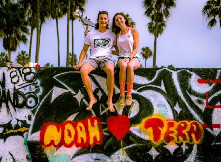 """Noah & Tera sitting on top of one of the art walls at Venice Beach in Southern California. Beneath them are spray painted """"bubble letters"""" reading """"Noah"""" and a red painted heart, and """"Tera"""""""