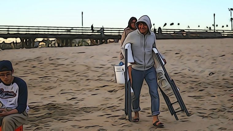 student carrying plastic folding chairs to the beach