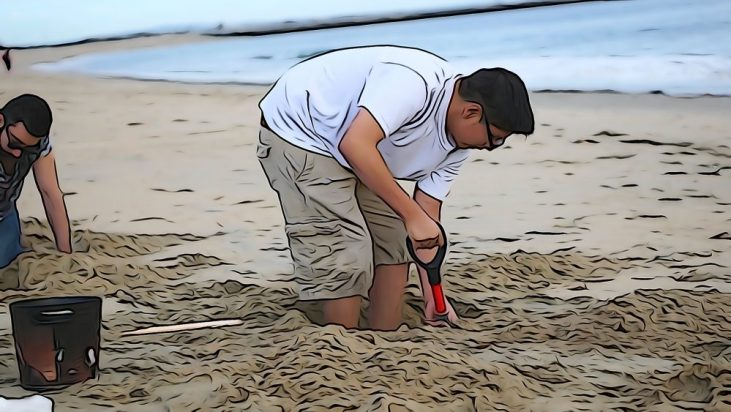 student digging a hole in the sand at the Seal Beach Pier