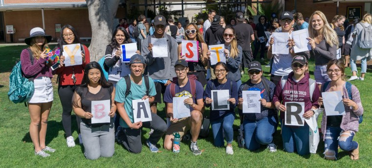 "a group of students, each holding an individual letter that together spell out ""My last DJ Ballers"""