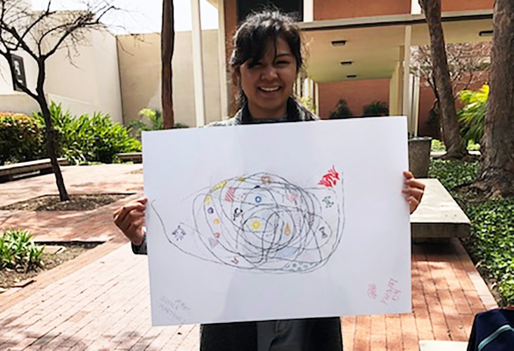 Phanary Om holding a large drawing and smiling