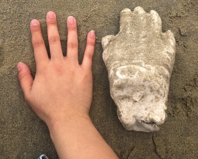 Photo of a hand next to a plaster cast reproduction of the hand