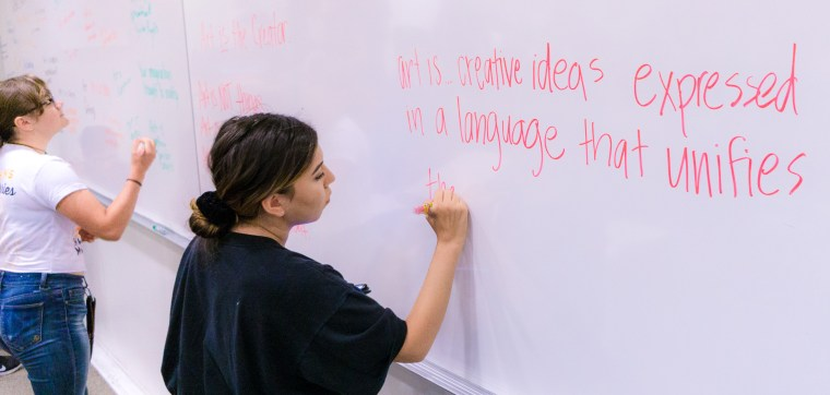 "students writing ideas about ""Art"" on the classroom white board"