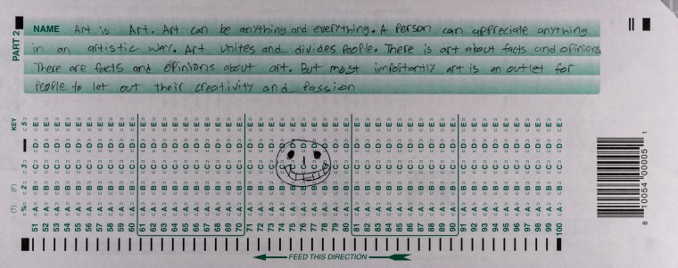 "Jeff Vintimilla's scantron midterm featuring a happy face with big teeth on the scantron grid and a text passage on the green stripes on the edge of the form, ""Art is art. Art can be anything and everything. A person can appreciate anything in an artistic way. Art unites and divides people. There is art about facts and opinions. There are facts and opinions about art. But most importantly art is an outlet for people to let out their creativity and passion."
