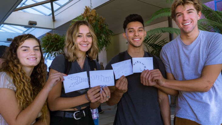 four students standing in the Long Beach State University, School of Art, Art Gallery Courtyard and holding 4x6 index cards on which each has drawn a part of a snake so that together the cards make one long snake illustration
