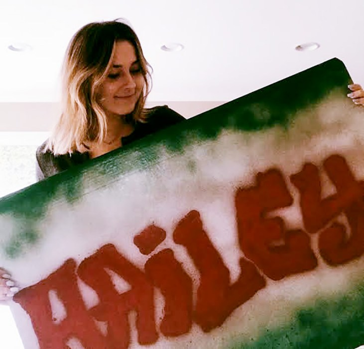 "nursing student Hailey Hairrell holding a large board with the name ""Hailey"" spray painted on it"