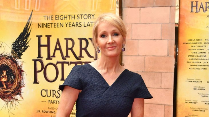 photo of author J. K. Rowling in front of a Harry Potter poster