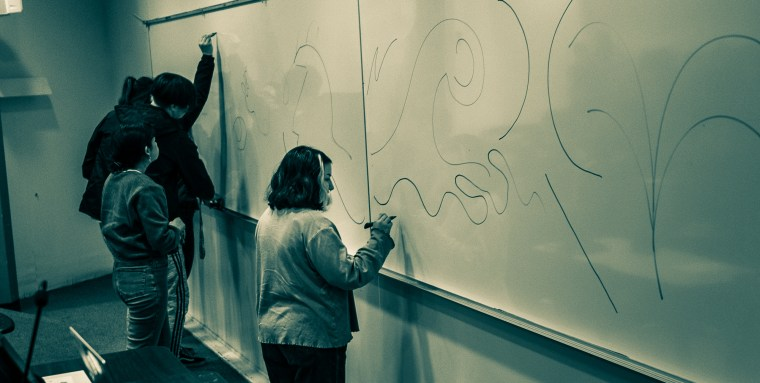 Students at the white board in Psy-150 drawing