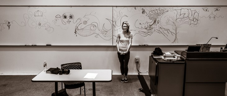 Lizzie Green stands in front of a wide, panoramic whiteboard mural