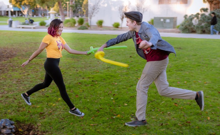 "Audrey Resella and Brian Freeman battle with ""balloon swords"" on the grass in front of the School of Art, Art Gallery Courtyard, at Long Beach State University"