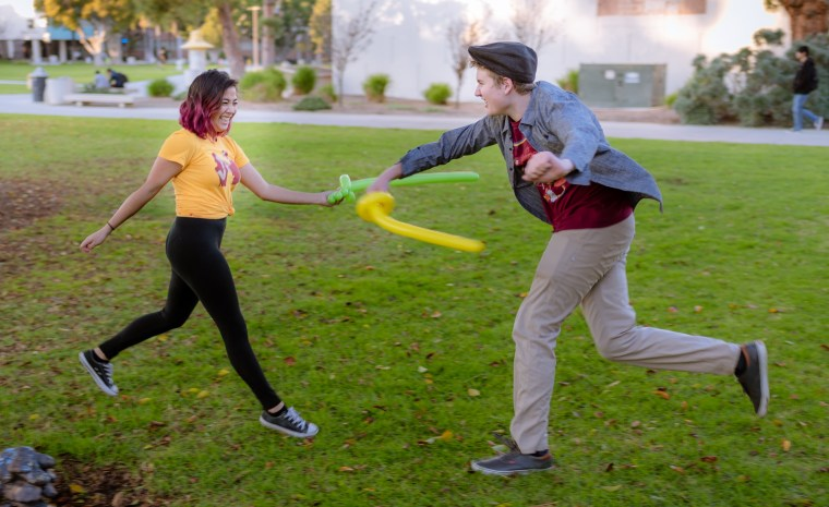 """Audrey Resella and Brian Freeman battle with """"balloon swords"""" on the grass in front of the School of Art, Art Gallery Courtyard, at Long Beach State University"""