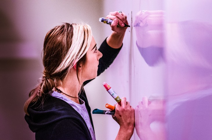 Artist Lizzie Green drawing on a whiteboard at Long Beach State University