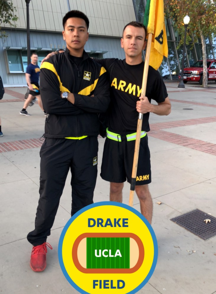 """Trenton Riemer in an """"ARMY"""" t-shirt and holding a flag at Drake Field at UCLA"""