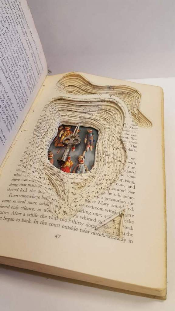 Image of an artist's book showing cut pages and inserted objects