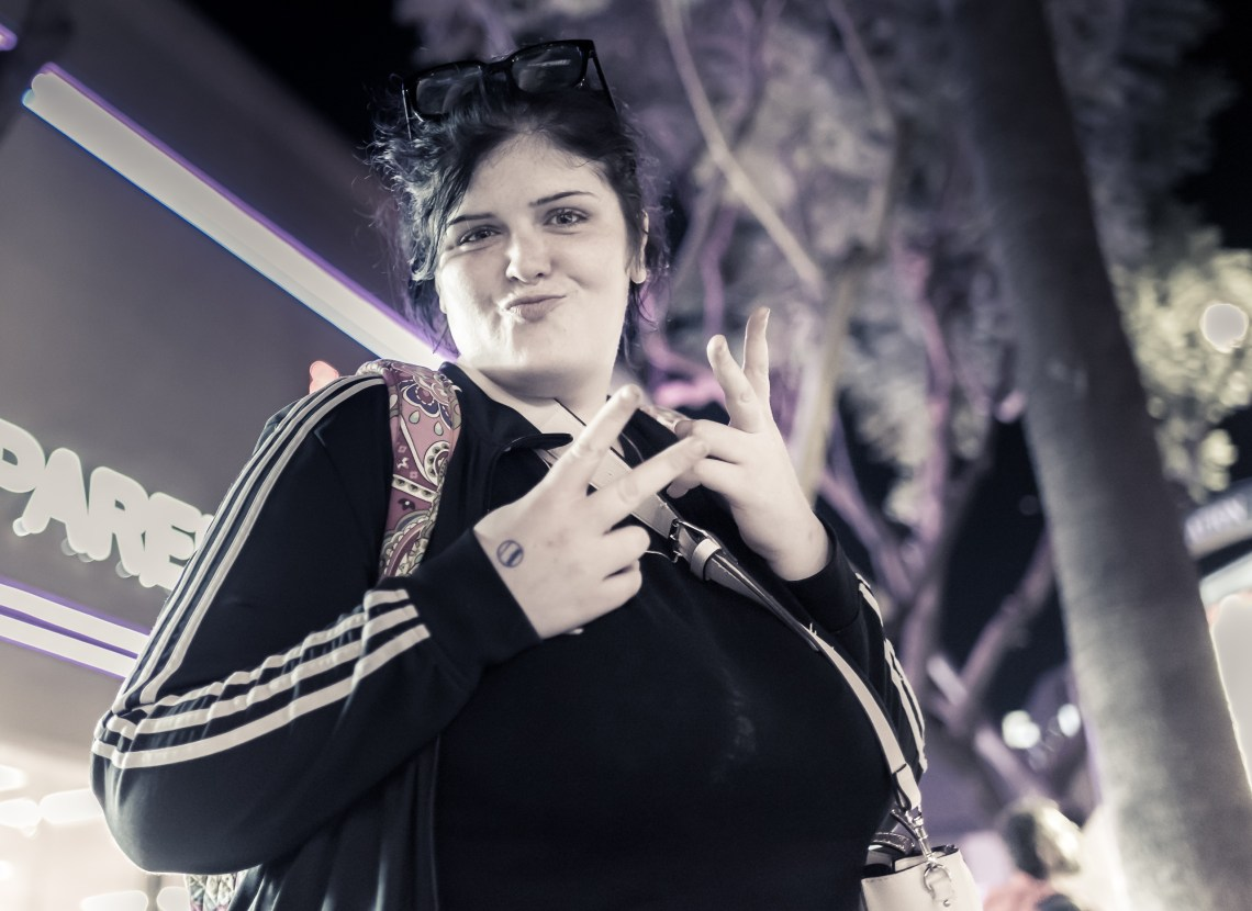 Rachel smiling through pursed lips and making peace signs with both hands. She's dressed in all black and stands against night on the street.