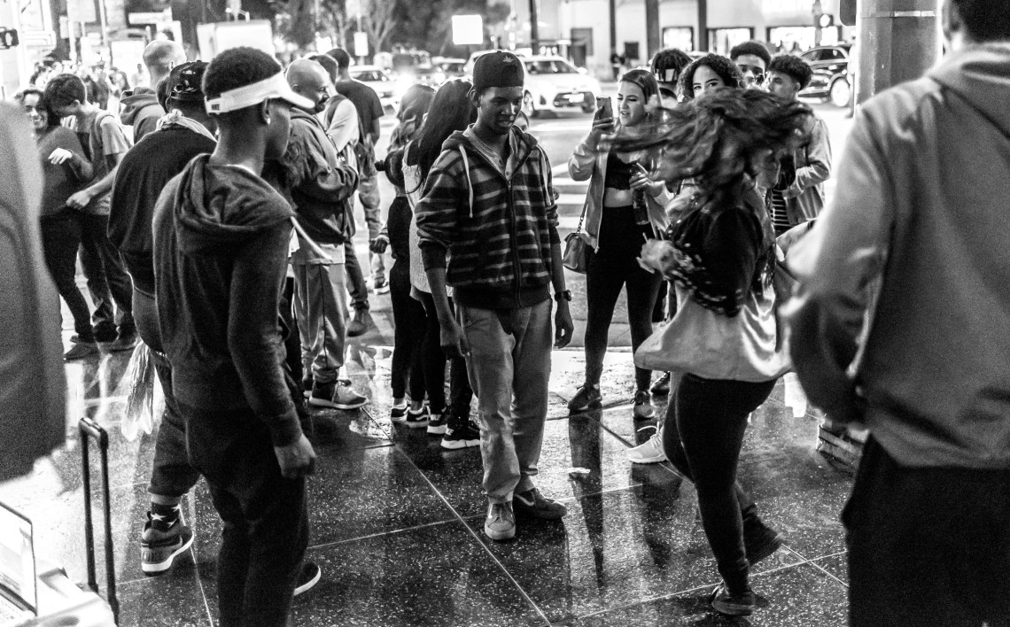 a crowd of people on the corner, some dancing some talking