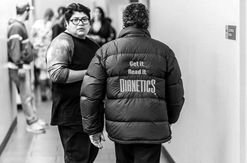 """a man walks down the restroom corridor at Hollywood & Highland wearing a large, down windbreaker. On the back large embroidered letters read """"Get it. Read it. Dianetics"""""""