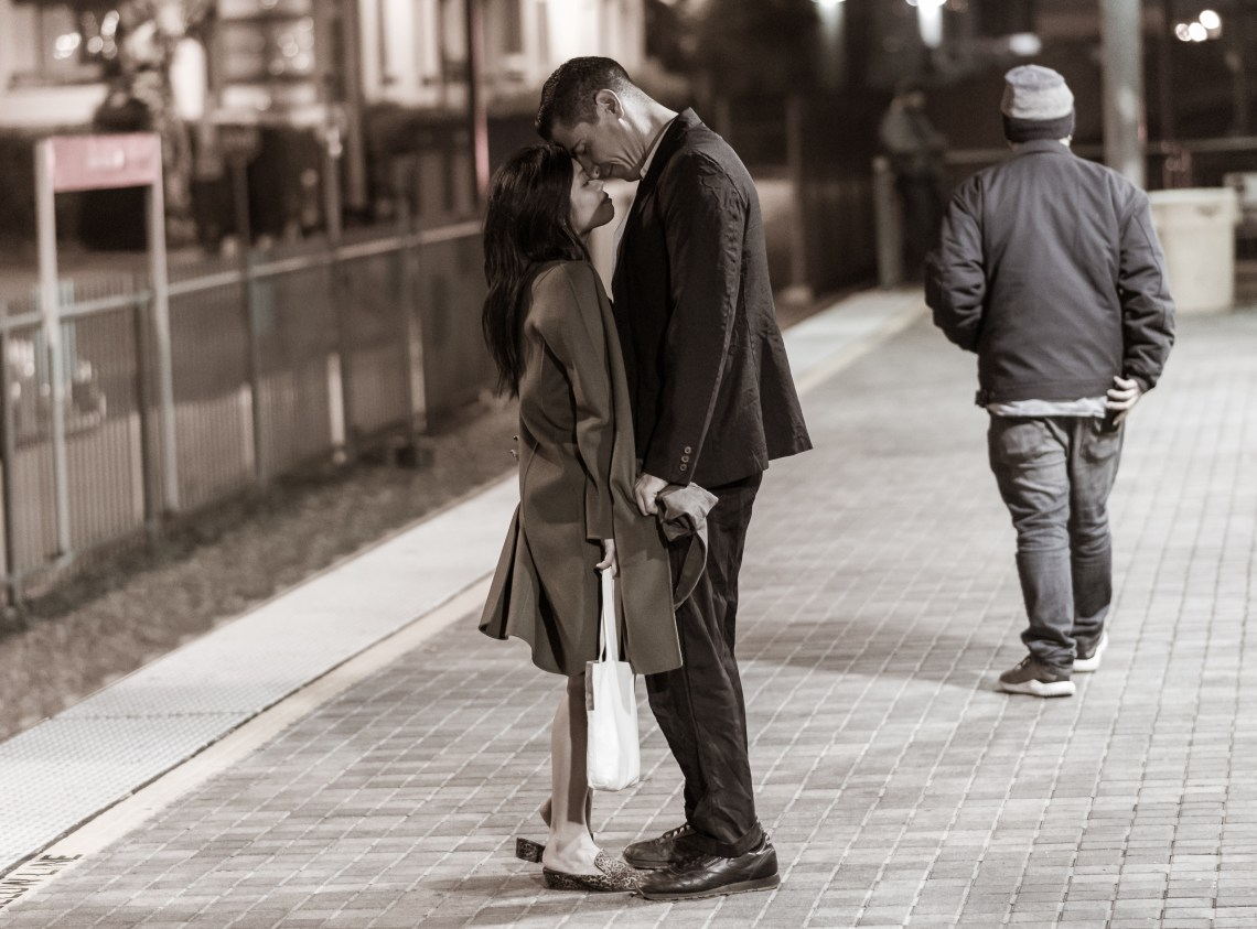 A man and a woman on the Gold Line platform at Union Station in Downtown Los Angeles. She wears an oversized coat which he holds the sleeves of as they press their heads to each other.