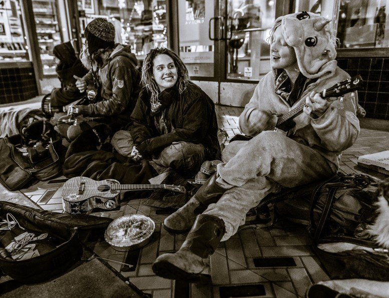 a group of people with food, blankets, guitars, and other materials huddle in the entrance to a storefront on Colorado Blvd in Pasadena on New Year's Eve. Some of them play guitars.