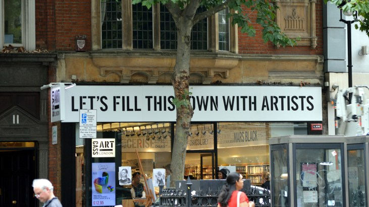 "photo of an art store with a large front sign ""Let's Fill This Town WIth Artists"""