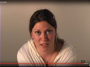 screencap from monologue video. Sarah Kelly in a white sweater addressing the camera