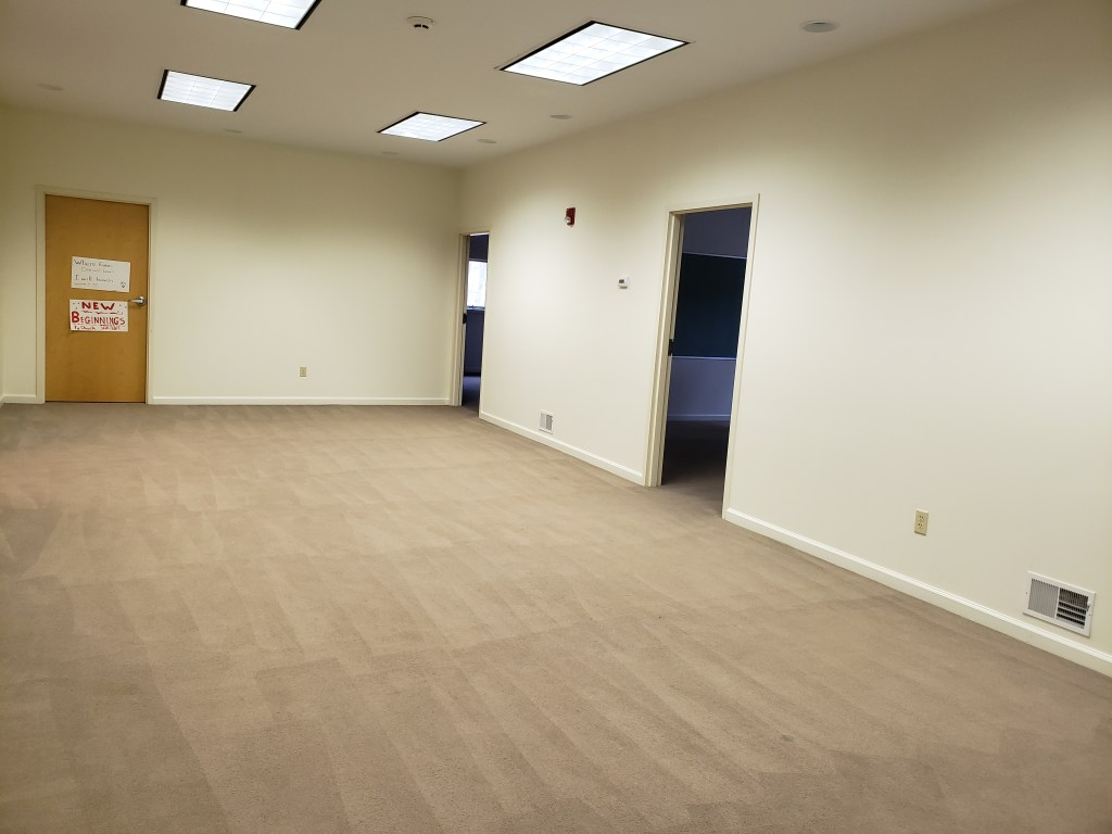 A long room with white walls, tan carpeting, fluorescent lighting, and several open doors.