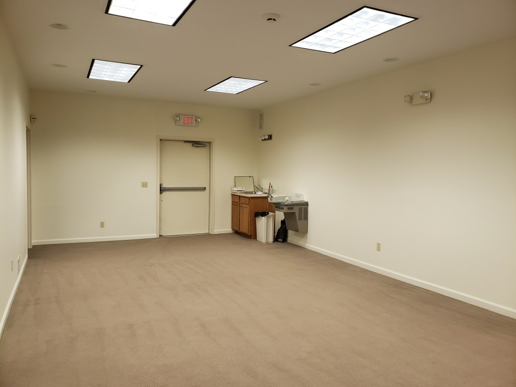 A long room with white walls, tan carpeting, a sink and water fountain in one corner, and an emergency exit door.