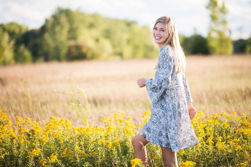 Grand Rapids girl in a dress smiles broadly as she walks through a fall West Michigan field for high school senior portraits