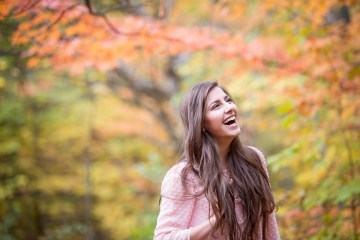 Grand Rapids senior portrait photographer captured a senior girl laughing surrounded by Michigan fall color