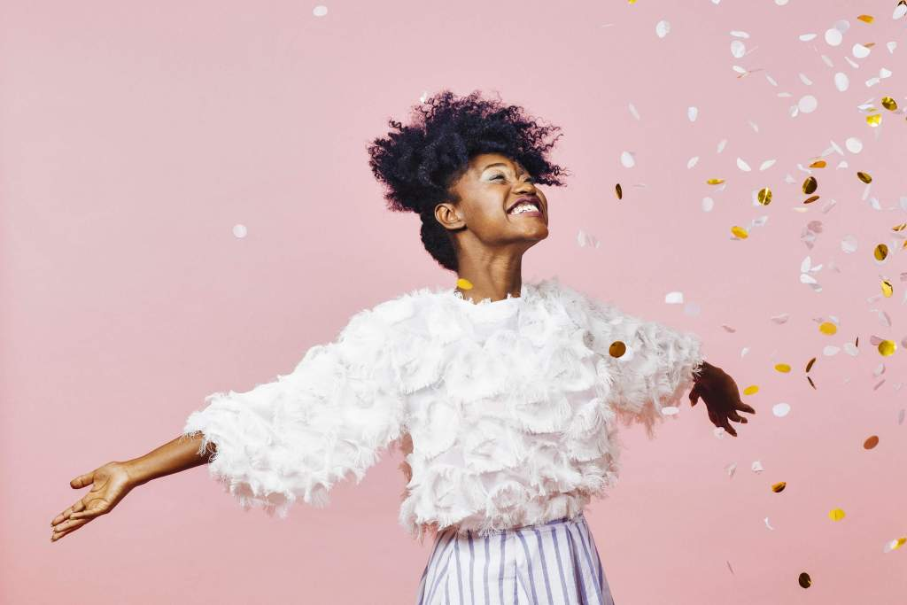 Woman in a white fuzzy sweater throwing gold confetti on a pink background