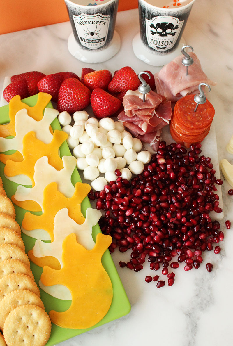 A selection of cheese and specialty meats with fruit for Halloween.