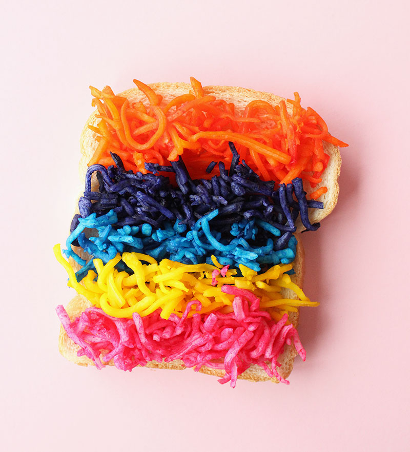 A piece of bread with rainbow colored cheese on it.