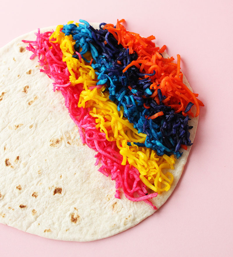 An assortment of cheese on a tortilla in colors of the rainbow.