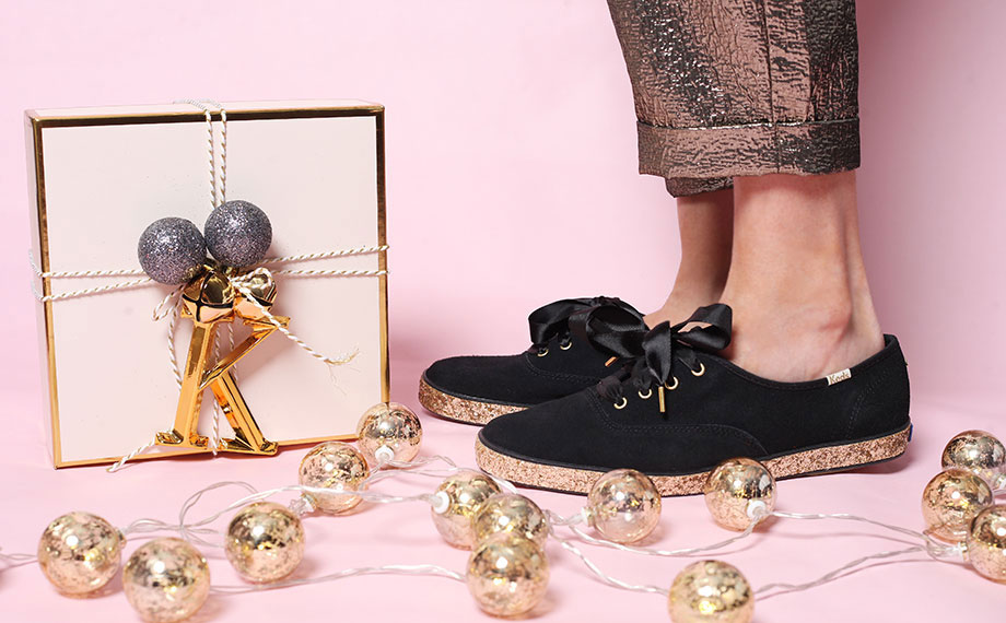 A pair of black and gold Keds x Kate Spade glitter shoes.
