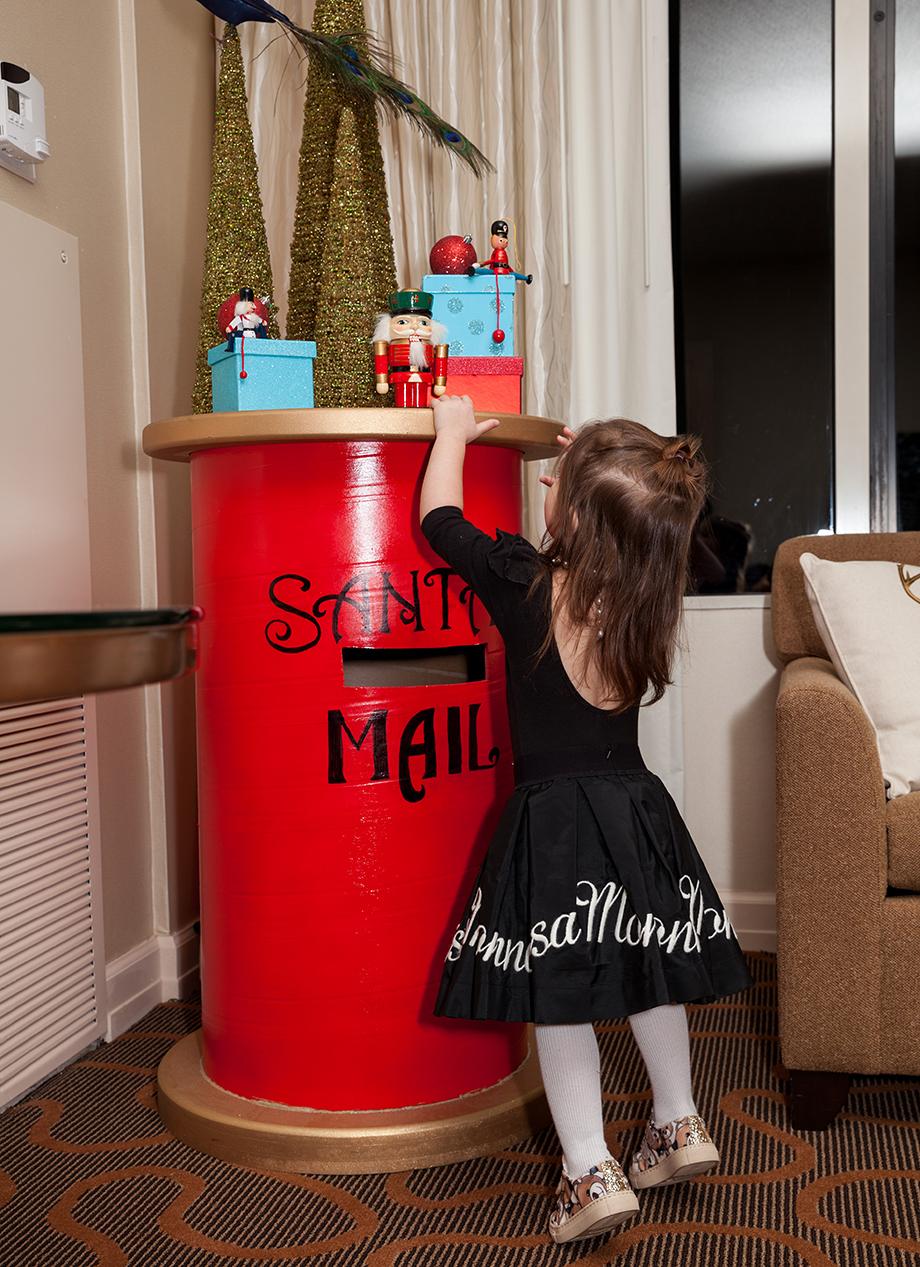 A little girl wearing a Mona Lisa skirt sends Santa a letter at the Swissotel.