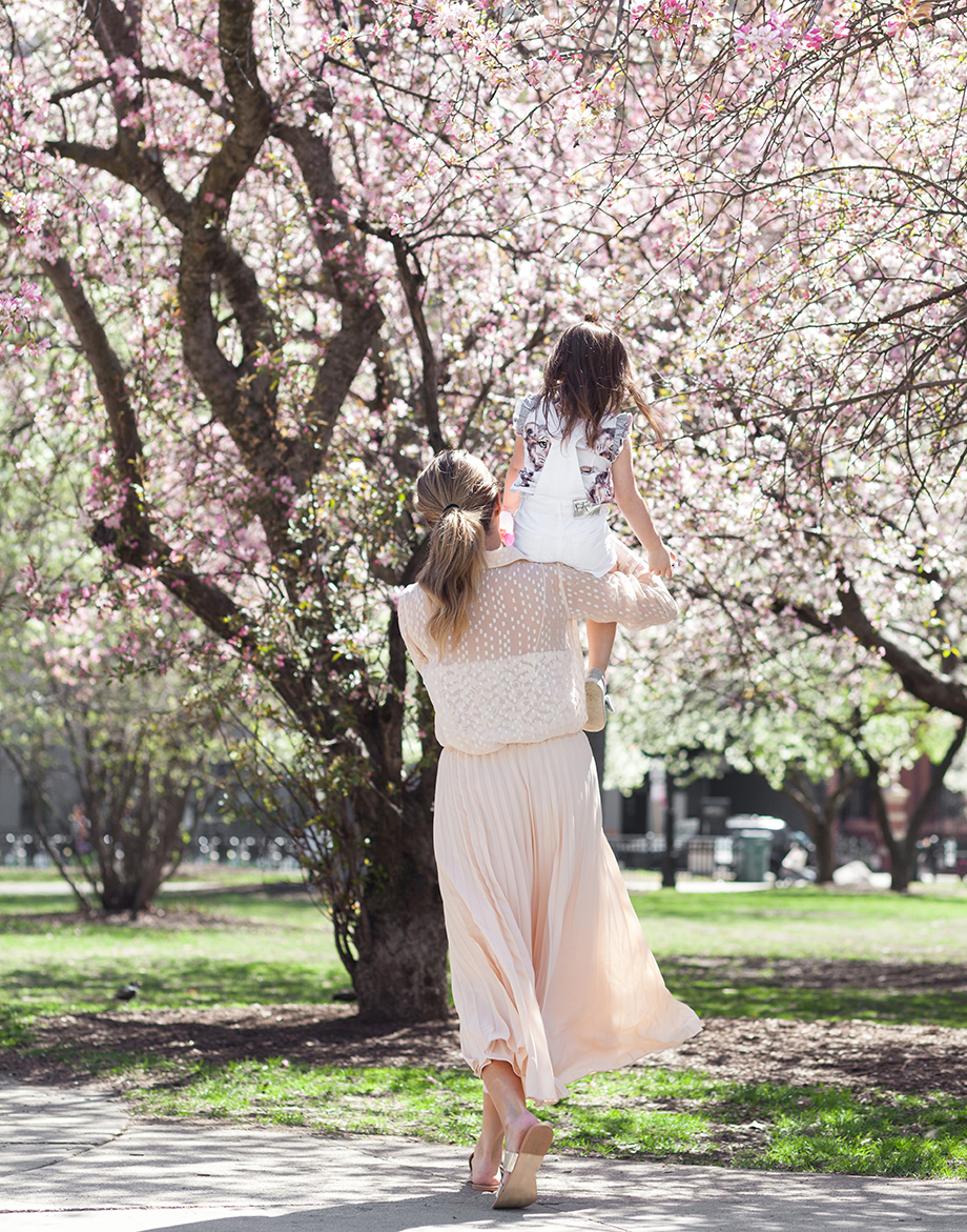 Corri McFadden and Zelda playing in the park in pastel pink outfits.