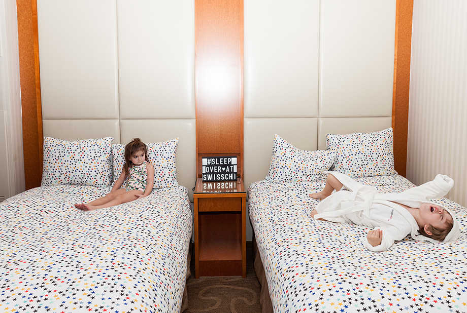 Two children playing at the Swissotel on bedding from The Land of Nod.