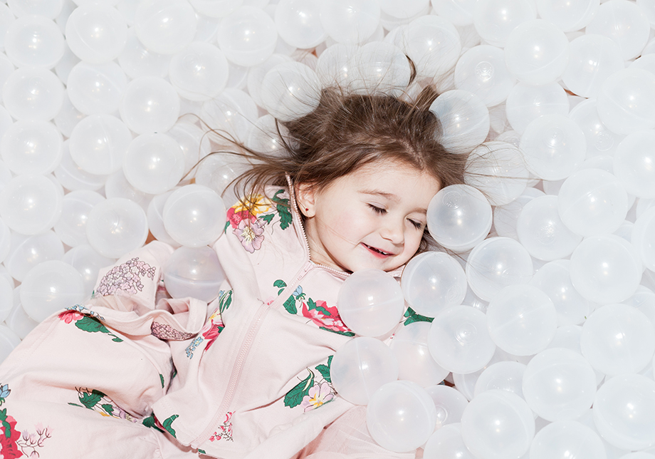 A little girl in a ball pit wearing a floral jacket at the 900 North Michigan Shops in Chicago.